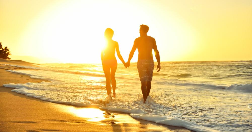 couple-walking-on-romantic-kauai-beach-at-sunset
