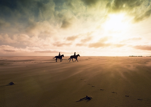 people-horseback-riding-on-the-beach-at-sunset