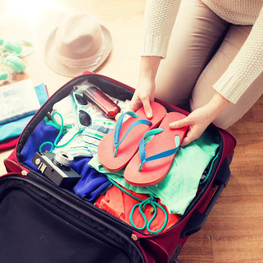 person-packing-a-suitcase-with-clothing-and-shoes